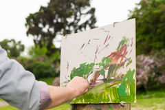 Male artist's hand painting a beautiful sketch of picture outdoo Stock Photography