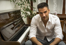 Male artist sitting next to his upright piano Stock Photography