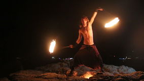 Male Artist of the spins fire poi on a rock stock video