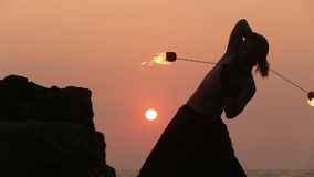 Male Artist of the spins fire poi on a rock stock footage
