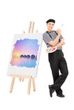 Male artist standing by a painting on an easel. Isolated on white background stock images