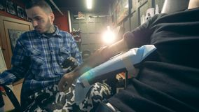 Male artist tattooing on a hand prosthesis, bionic arm. 4K stock video footage