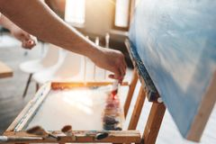 Free Male Artist Work In Art Studio. Hand Of Painter Closeup Squeezing Paint From A Tube On A Palette Royalty Free Stock Images - 114472239