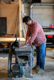 Male artist works with a wooden board at the planer, joiner's sh. Carpenter working with  big electric planer on wooden plank works at the planer, joiner's shop Stock Photography