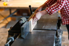 Male artist works with a wooden board at the planer, joiner's sh. Carpenter working with  big electric planer on wooden plank works at the planer, joiner's shop Stock Images