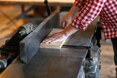 Male artist works with a wooden board at the planer, joiner's sh. Carpenter working with  big electric planer on wooden plank works at the planer, joiner's shop Royalty Free Stock Image