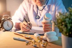 Male doctor looking at pill bottle working in hospital. Male Asian doctor looking at pill bottle on his hand writing on clipboard. Doctor working with medicine Stock Photos