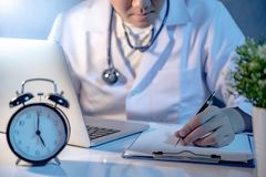 Male Asian doctor working with laptop and clipboard in hospital royalty free stock photo