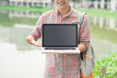 Male asian hand showing laptop screen outdoors.  Royalty Free Stock Photo