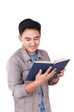 Male Asian Student Reading Book. Photo image portrait of a cute young Asian male student standing and smiling while reading a book, isolated on white Stock Photography