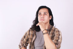 Male Asian Student Thinking. Photo image portrait of a cute young Asian male student with long hair, looking up seriously, touching his chin and thinking Stock Image
