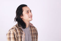 Male Asian Student Thinking. Photo image portrait of a cute young Asian male student with long hair, smiling, looking up and thinking Stock Images