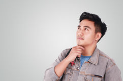 Male Asian Student Thinking. Photo image portrait of a cute young Asian male student standing, looking up and thinking Royalty Free Stock Images