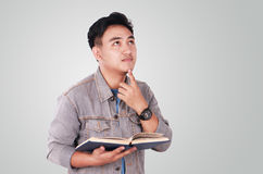 Male Asian Student Thinking While Reading Book. Photo image portrait of a cute young Asian male student standing, looking up and thinking while reading a book Royalty Free Stock Image