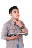 Male Asian Student Thinking While Reading Book. Photo image portrait of a cute young Asian male student standing, looking up and thinking while reading a book Stock Images