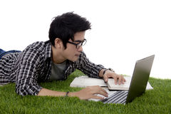 Male Asian student uses laptop on grass. Male Asian college student lying on the grass while studying with a laptop and books, isolated on white background Royalty Free Stock Image
