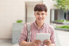 Male asian student using digital tablet in campus.  Royalty Free Stock Image