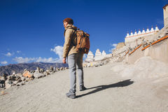 Male Asian traveler walking uphill on sand dune leading to monastery in Leh, Ladakh, India.  Stock Images
