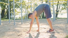Male Athlet does Morning Exercise Outdoors. Close up slow motion. Workout standing on the is located near the lake with water and trees on the shore. Healthy stock images