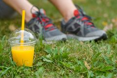 Male athlet takes a break. After doing sports in the park on the juicy grass. Expensive sneakers in the blurred background. A plastic cup of smoothie in focus stock photography