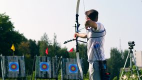 Male athlete aiming at target with a bow. 4K stock video footage