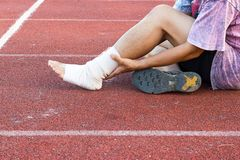 Male athlete applying compression bandage onto ankle injury. Of a football player, Sports injuries stock photo