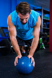 Male athlete with ball in gym. Male athlete with ball while exercising in gym Royalty Free Stock Photos