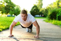 A male athlete in black shorts and a white T-shirt does push-ups. The concept of a healthy lifestyle. Strength and. A male athlete in black shorts and white T Stock Image