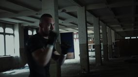 Male Athlete boxer punching bag with dramatic edgy lighting in a dark studio. Kickboxing stock video footage