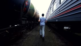 Male athlete boxer runs among the trains. Male boxer athlete runs among the trains on a cloudy day Royalty Free Stock Images