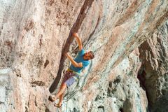 Male Athlete climbing severe overhanging high orange Rock Royalty Free Stock Photo