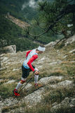 Male athlete climbs on foot uphill Stock Photo
