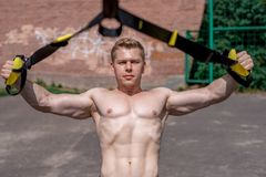 Male athlete close-up, trains nature in city, summer trx training, Feel your strength and balance, motivation, tanned. Male athlete close-up, trains in nature in Royalty Free Stock Image