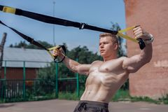 Male athlete close-up, trains nature city, summer trx training, Feel your strength and balance, motivation, tanned skin. Male athlete close-up, trains in nature Stock Image