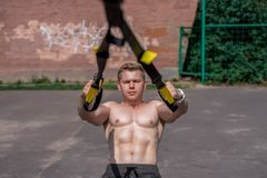 Male athlete close-up, trains nature in city, summer trx training, Feel your strength and balance, motivation, tanned. Male athlete close-up, trains in nature in Royalty Free Stock Photos