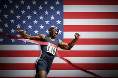 Male athlete crossing finish line against American flag Royalty Free Stock Image
