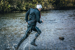 Male athlete crossing the river on rocks side view. Beloretsk, Russia - September 26, 2015: male athlete crossing the river on rocks side view during marathon stock photography