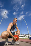 Male athlete crouching with discus, portrait, low angle view Royalty Free Stock Photos