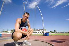 Male athlete crouching with discus, portrait, low angle view Stock Image