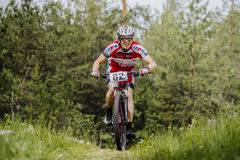 Male athlete a cyclist uphill in forest. Chelyabinsk, Russia - June 5, 2016: male athlete a cyclist uphill in forest during cross-country race New energy Stock Photos