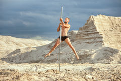 Male athlete is dancing on a pole. Male athlete dances on a pole among the sand in the desert Royalty Free Stock Photo