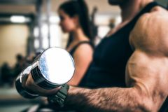 Male athlete doing biceps exercise with dumbbells. Bodybuilder trains biceps with dumbels in gym. Fitness and crossfit concept. Close-up Royalty Free Stock Photography