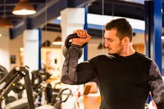 Male athlete doing biceps exercise with weight. Bodybuilder trains biceps with weight. Fitness and crossfit concept. Close-up stock photography