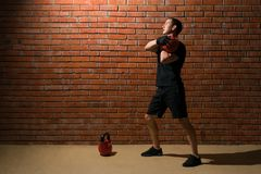 Male athlete doing an exercise with weights in a gym on a brick wall background Stock Photos