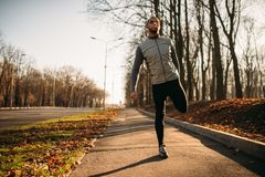 Male athlete doing exercise on workout outdoors. Runner in sportswear on training in park Stock Photos