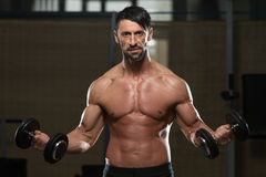 Male Athlete Doing Heavy Weight Exercise For Biceps Stock Photography