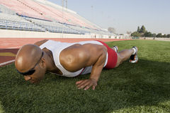 Male Athlete Doing Push-Up Before Race. Full length of an African American male athlete makes push-up before race Stock Photos
