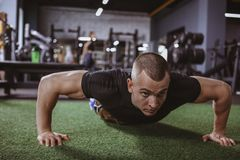 Athletic muscular man exercising at the gym royalty free stock image