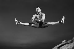 Male athlete doing splits in the air while jumping. Monochrome shot of a handsome fit young male gymnast jumping high doing splits in the air copyspace sports Stock Image