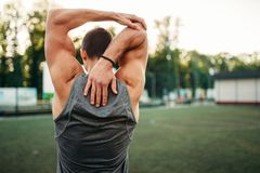 Male athlete doing stretching exercise, back view. Muscular male athlete doing stretching exercise, back view, fitness workout. Strong sportsman in park Royalty Free Stock Photography